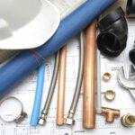 ferramentas, materiais hidráulicos e um capacete sobre uma mesa